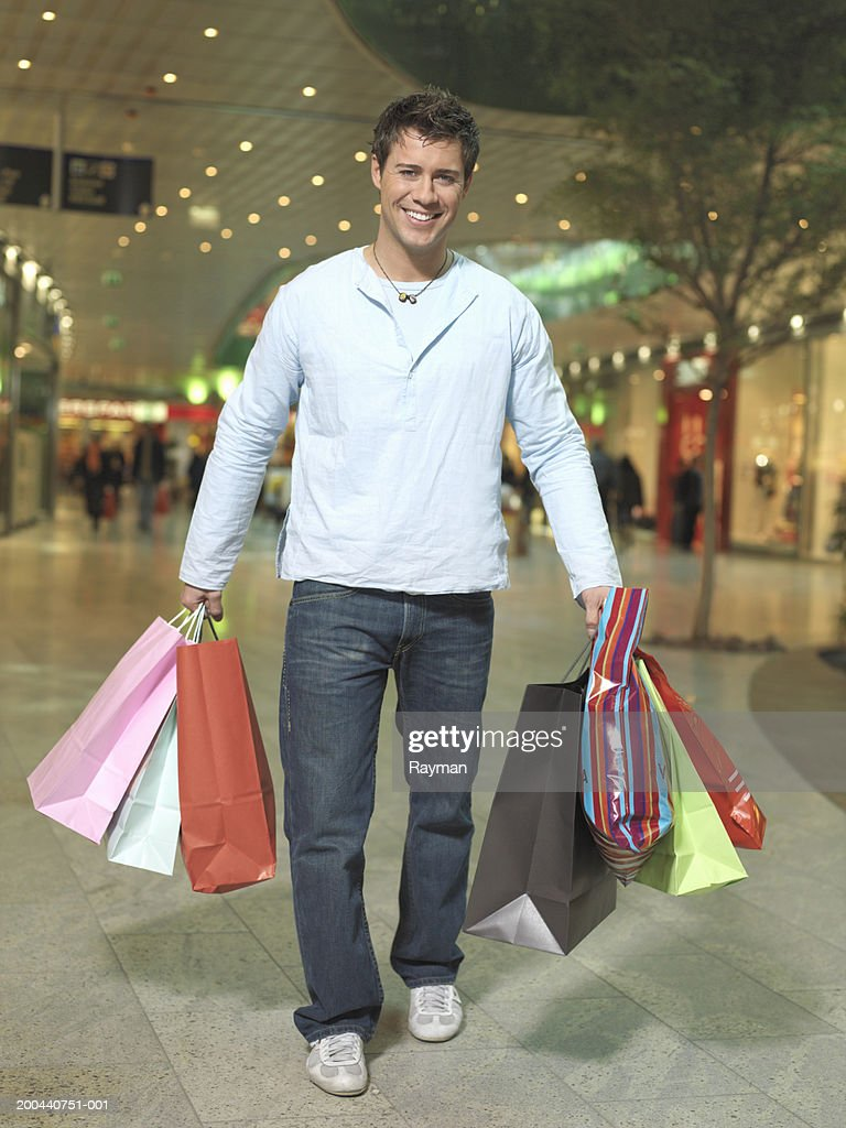 Man Carrying Bags Walking In Shopping Centre Smiling Portrait Stock Photo
