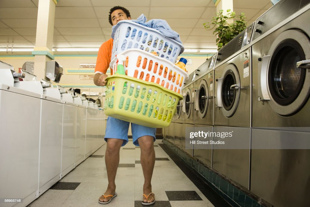 Man carrying baskets of clothes in launderette : Stock Photo
