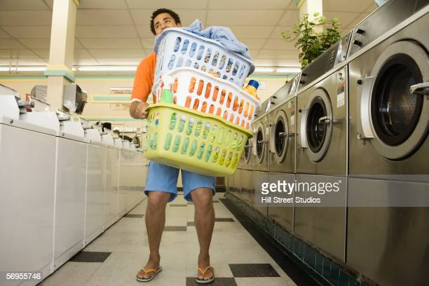 Man carrying baskets of clothes in launderette