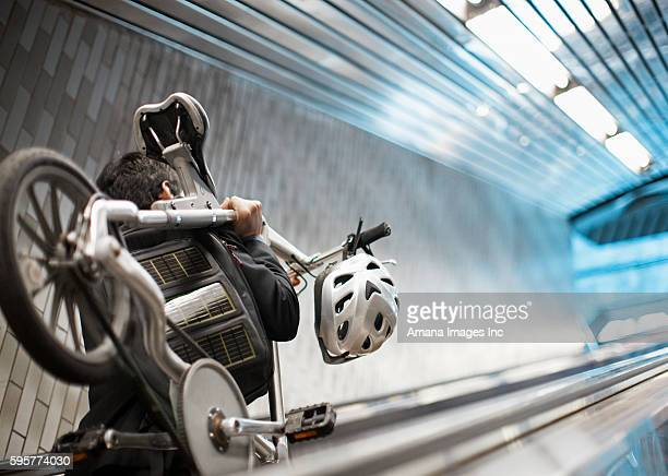 Man Carrying Bicycle on Escalator