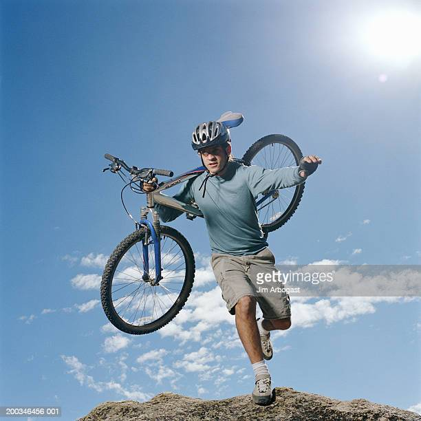 Man carrying bicycle on shoulder on rocky terrain, low angle view
