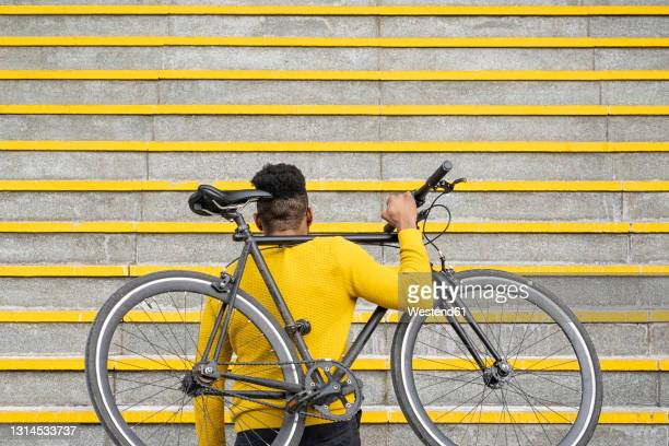 man carrying bicycle on shoulder on staircase - staircase stock pictures, royalty-free photos & images