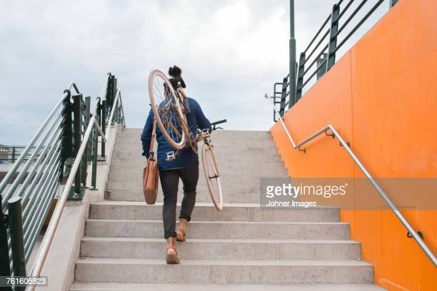 man carrying bicycle on steps - durability stock photos and pictures