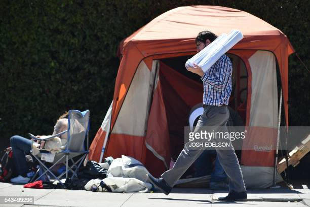 A man carrying blueprints passes a homeless encampment in downtown San Francisco California on June 2016 Homelessness is on the rise in the city...