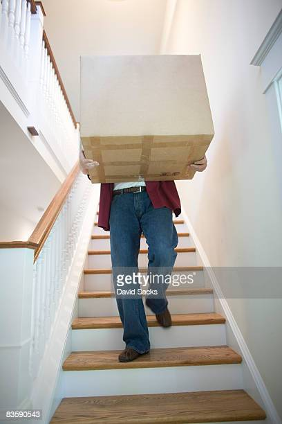Man carrying box down stairs