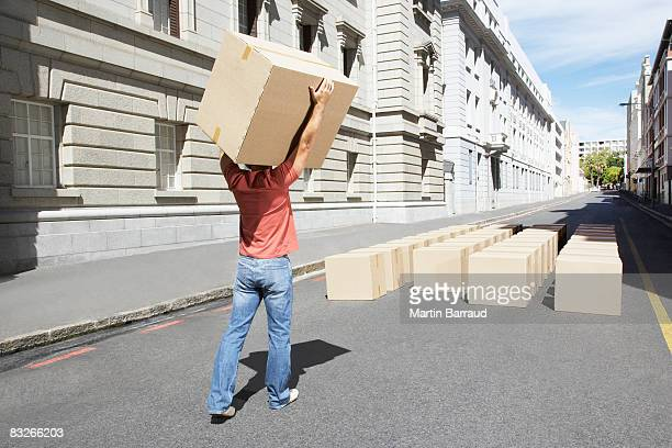 man carrying box in roadway - same action stock photos and pictures