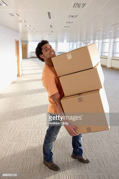 Man carrying boxes in empty office
