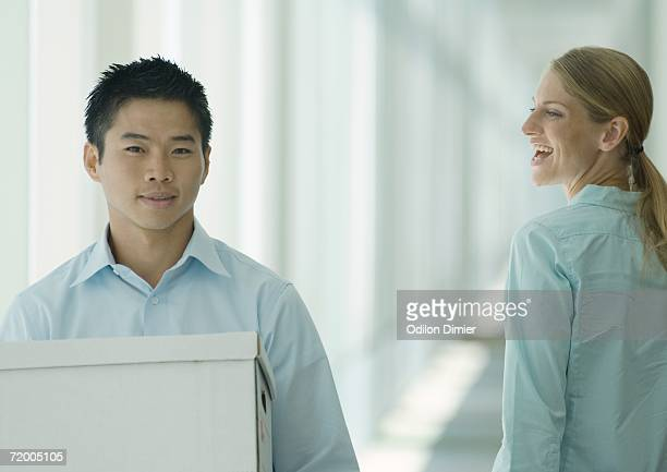 man carrying boxes in hallway, female colleague watching - moving past stock photos and pictures