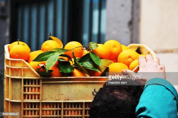 Man carrying boxes of fruit (Fresh organic oranges)