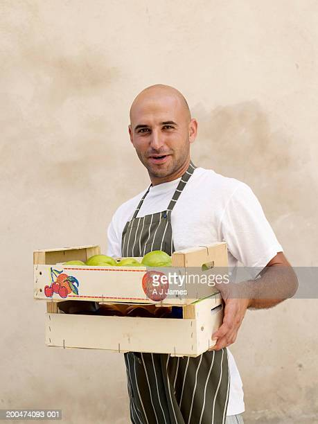 Man carrying boxes of fruit, portrait