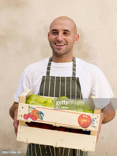 Man carrying boxes of fruit, smiling