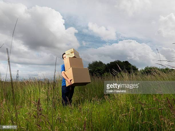 man carrying boxes through field