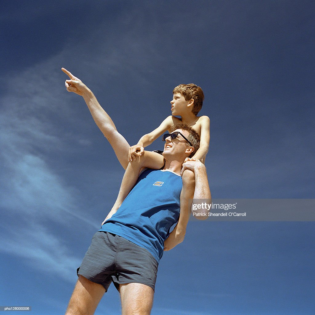 Man carrying boy on shoulders, outside, low angle view : Stockfoto