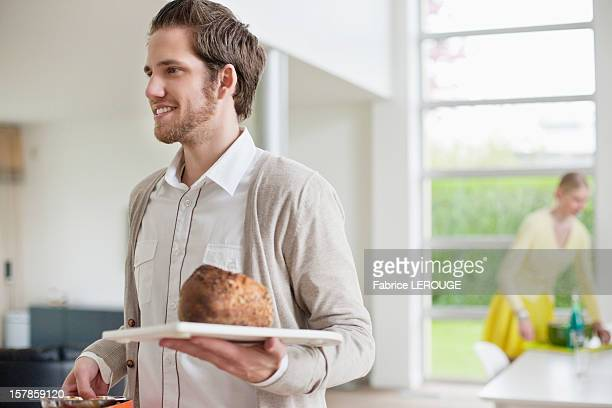 Man carrying bread on a tray
