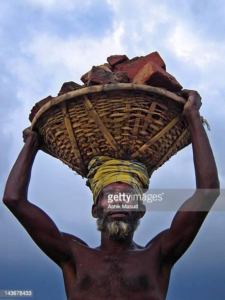 Man carrying bricks on his head