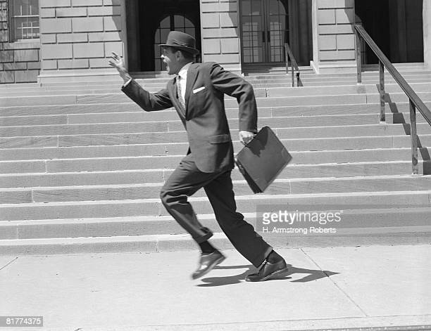 Man carrying briefcase, running past stairs, low section. (Photo by H. Armstrong Roberts/Retrofile/Getty Images)