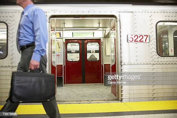 man carrying briefcase, side view, subway train in background - legs spread open stock photos and pictures