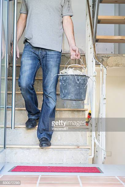 Man carrying bucket with rubble during house renovation