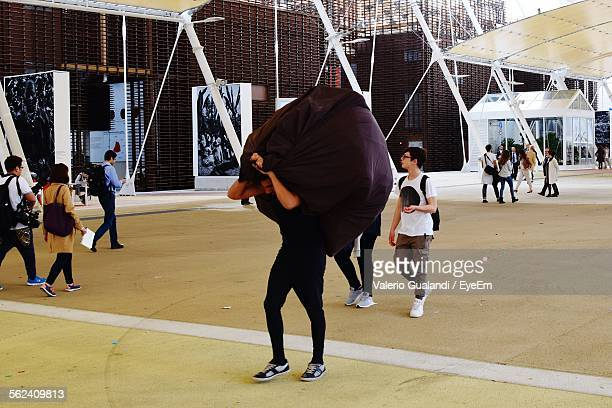 Man Carrying Burden While Walking On Street By Building