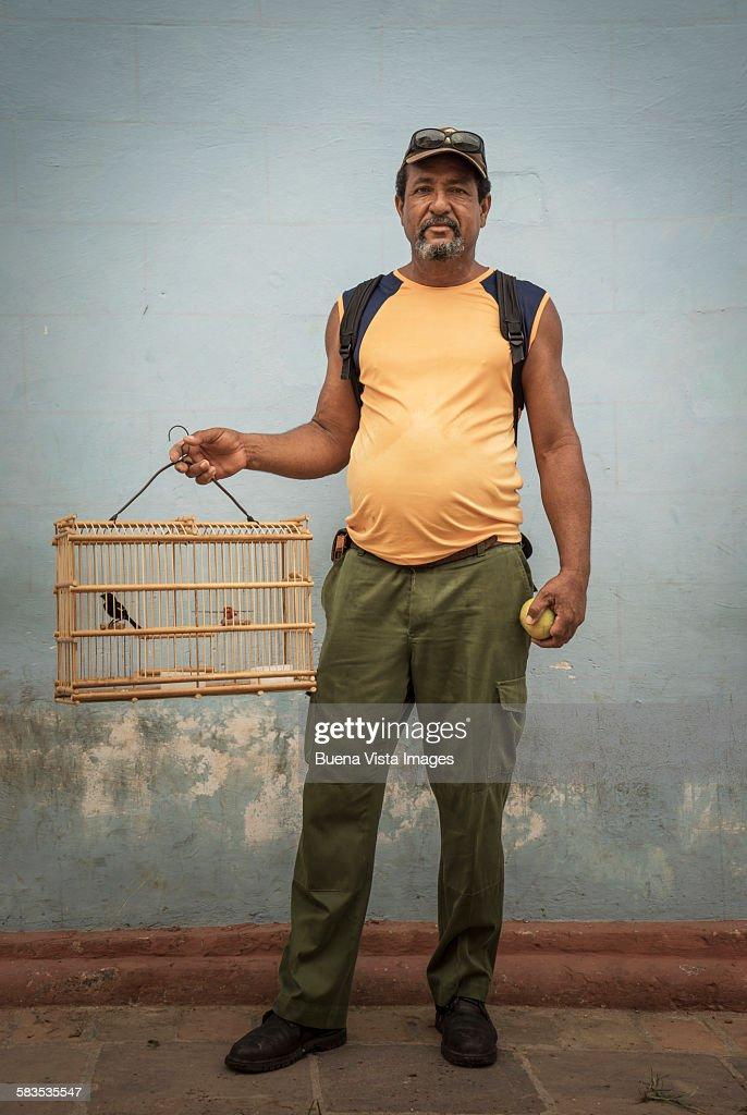 Man carrying caged pet bird : Stock Photo