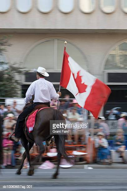 man carrying canadina flag on horse at calgary stampede parade - calgary stampede stock pictures, royalty-free photos & images