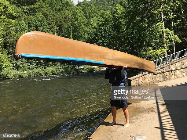 man carrying canoe on pier by river - carrying stock pictures, royalty-free photos & images