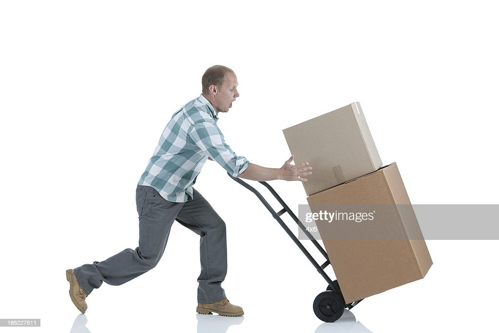 Man carrying cardboard boxes in a warehouse : Stock Photo