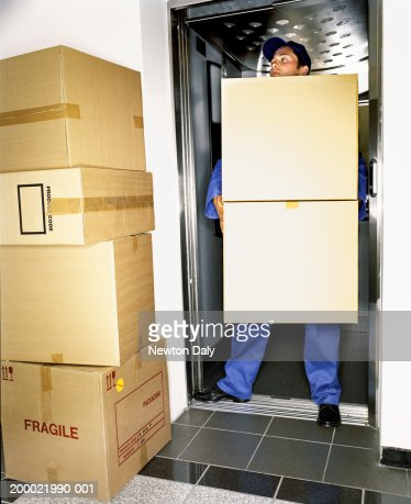 man carrying cardboard boxes standing in lift doorway stock photo getty images. Black Bedroom Furniture Sets. Home Design Ideas