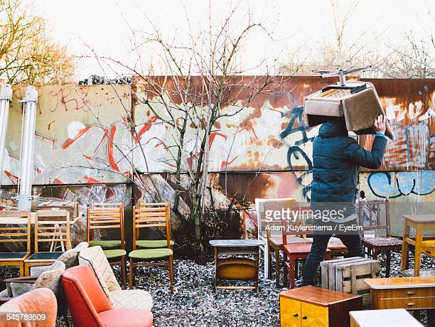 man carrying chair at flohmarkt am mauerpark - flea market stock pictures, royalty-free photos & images