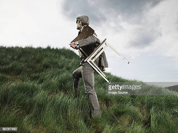 Man carrying chair through field
