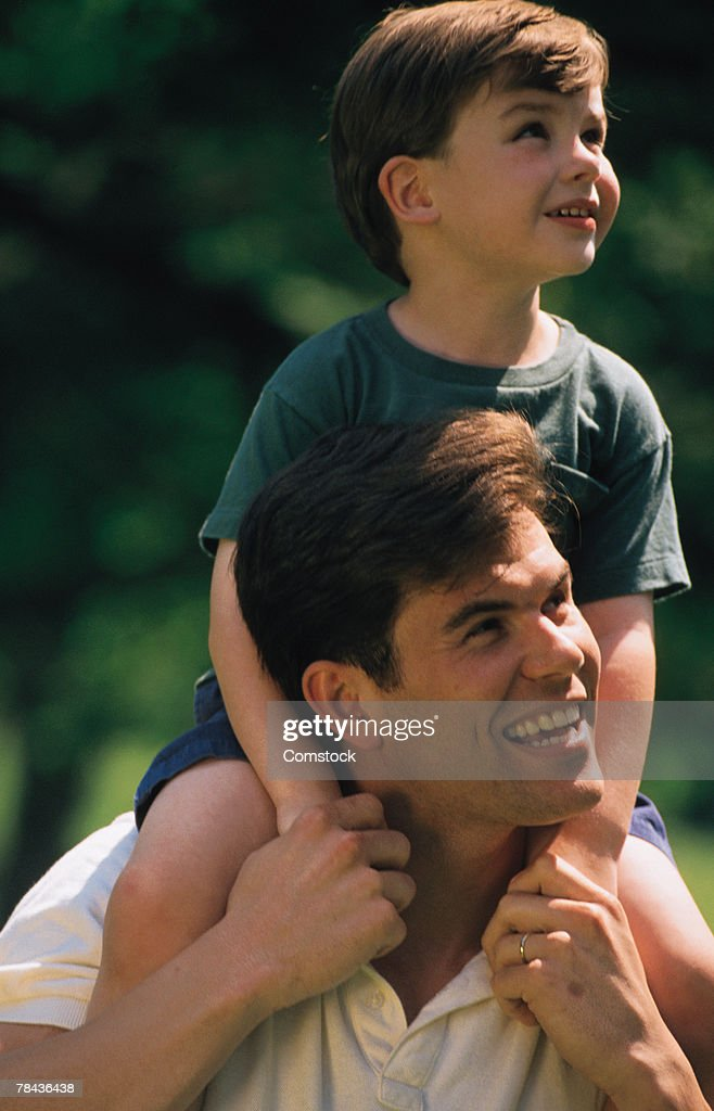 Man carrying child on shoulders : Stockfoto