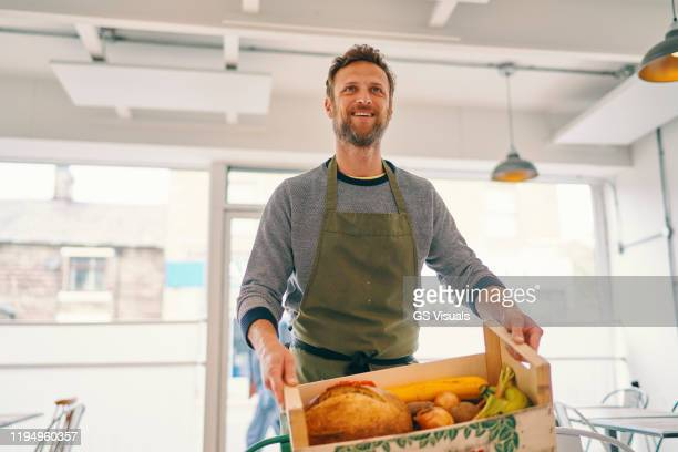 man carrying crate of food supply into restaurant - owner stock pictures, royalty-free photos & images