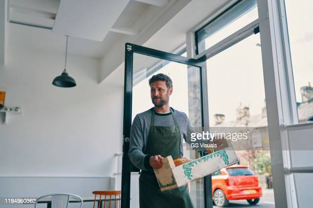 man carrying crate of food supply into restaurant - business stock pictures, royalty-free photos & images