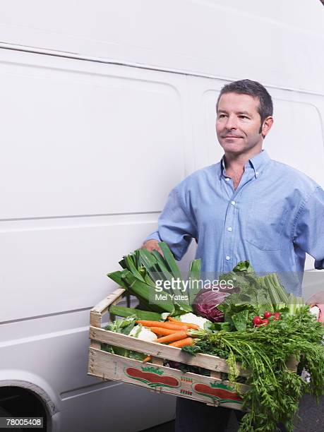 Man carrying crate of vegetables from van