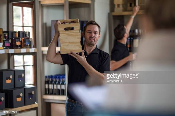 Man carrying crate of wine in shop