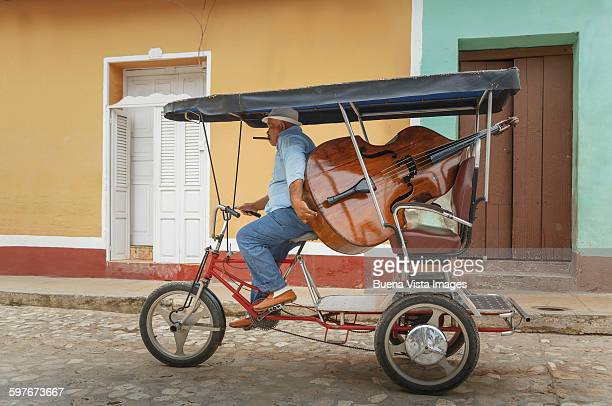 Man carrying double bass on a tricycle