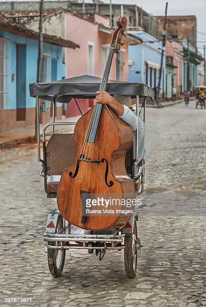 man carrying double bass on a tricycle - trinidad cuba stockfoto's en -beelden