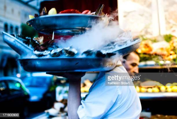 Man carrying double platter of smoking fresh fish in Marais taken at dusk