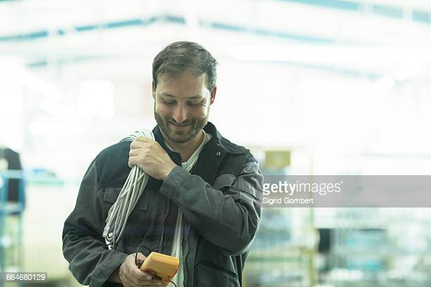 man carrying electrical cable and test meter - sigrid gombert stock-fotos und bilder