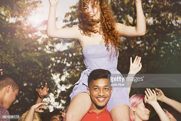 Man carrying female friends while enjoying party at yard