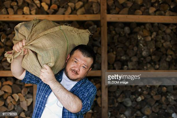 Man carrying firewood on shoulder