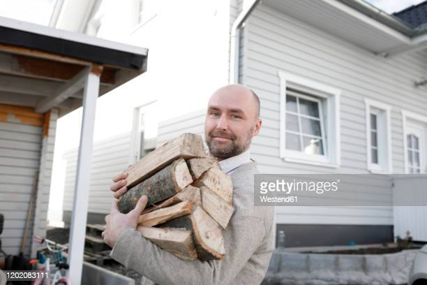 man carrying firewood - firewood stock pictures, royalty-free photos & images
