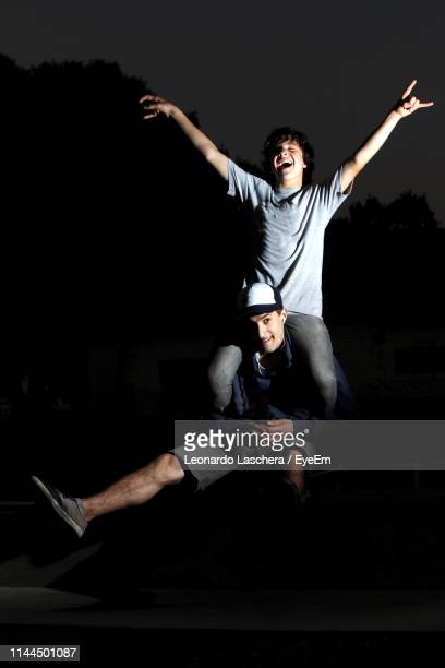 man carrying friend on shoulders at night - adults only stock pictures, royalty-free photos & images