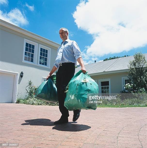 man carrying garbage bags - seulement des adultes photos et images de collection