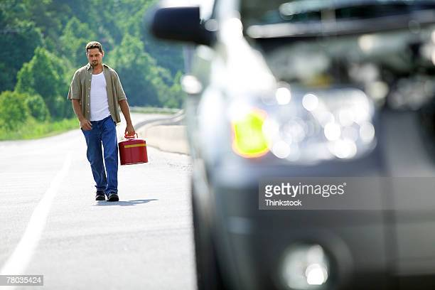 Man carrying gas can back to car