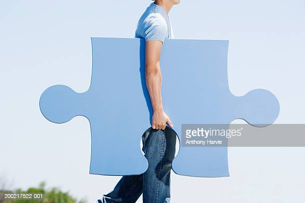 Man carrying giant jigsaw piece under arm, side view