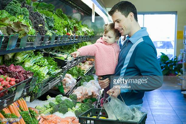 Man carrying girl and basket in supermarket, half length
