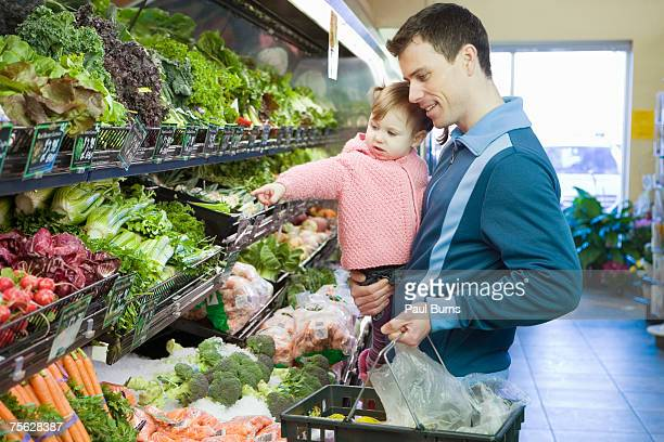 man carrying girl (18-21 months) and basket in supermarket, half length - produce aisle stock photos and pictures