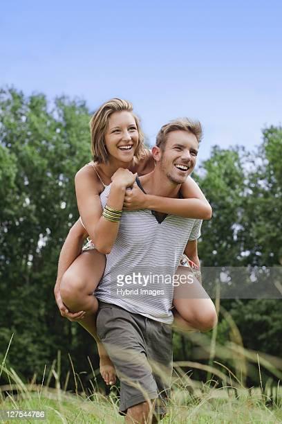 Man carrying girlfriend in field