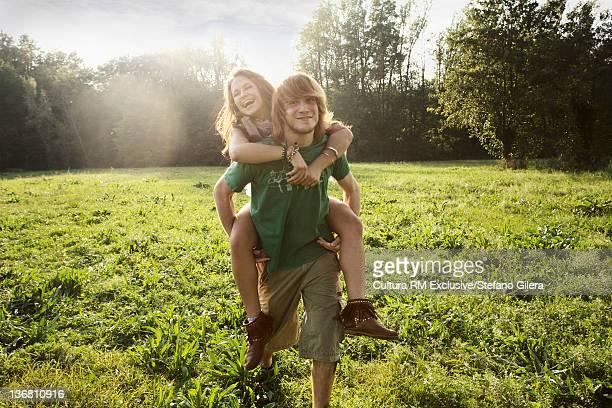 Man carrying girlfriend in rural field